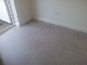 Polyflor Colonia Luxury Vinyl Tile <br />Colour Fossil Limestone with a Ice White feature strip installed into<br />a kitchen/Dining Room